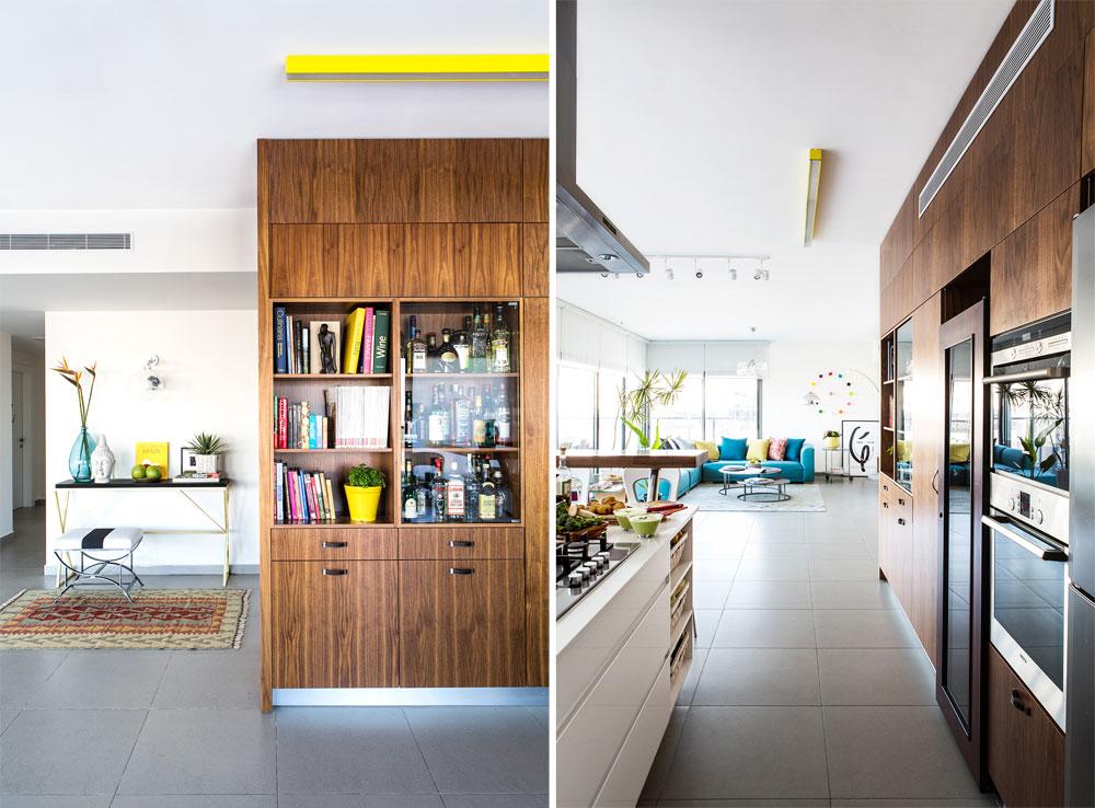 מימין: בקיר ארונות המטבח שובצו מכשירי החשמל, מקרר יינות ומקום של כבוד לאוסף בקבוקי האלכוהול של בעלי הבית. משמאל: מבט לאוסף הבקבוקים, שמוגן בדלתות זכוכית, ולספריית הבישול. מאחור נראות פינה מעוצבת במבואה והכניסה למסדרון המוביל לחדרי השינה (צילום: איתי בנית. סטיילינג: יעל קטורזה (סטודיו passe-par-tout))