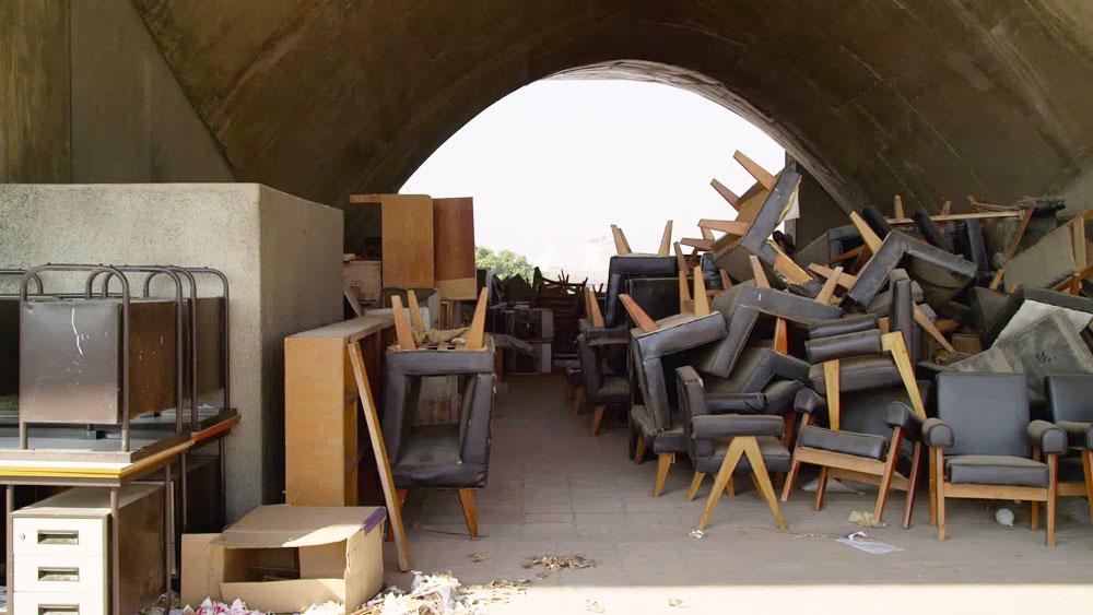 הרהיטים נערמו כגרוטאות בפינות נטושות, מופקרים לאבק ולעיתים אף לשמש הקופחת. צילום נוסף מתוך הסרט שמוצג במרכז לאמנות עכשווית בתל אביב (צילום: Amie Siegel)