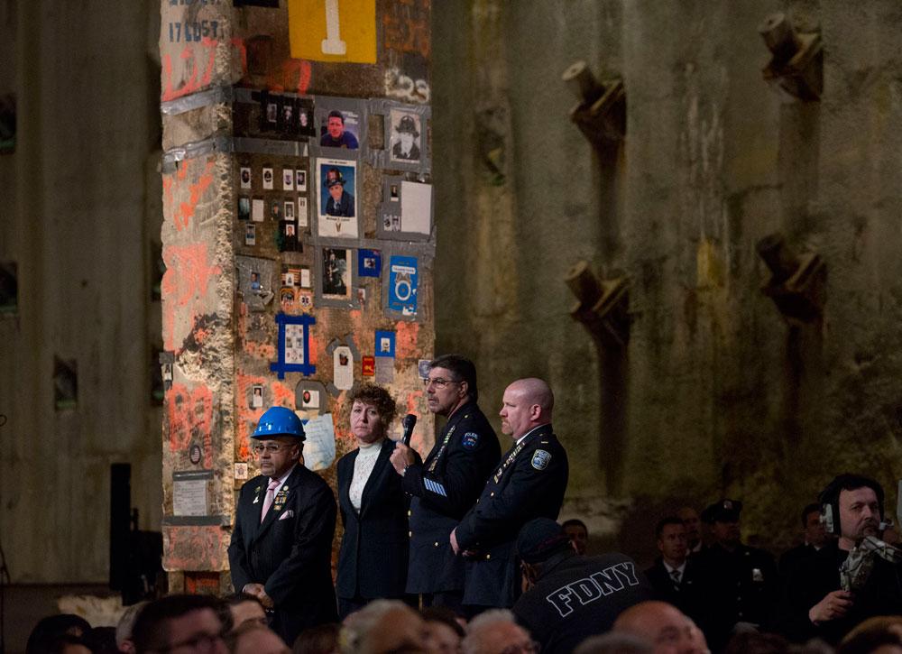 אנשי כיבוי וחילוץ בטקס. ברקע: העמוד האחרון של התאומים שהפך לקיר זיכרון במהלך פינוי האתר (צילום: Jin Lee)