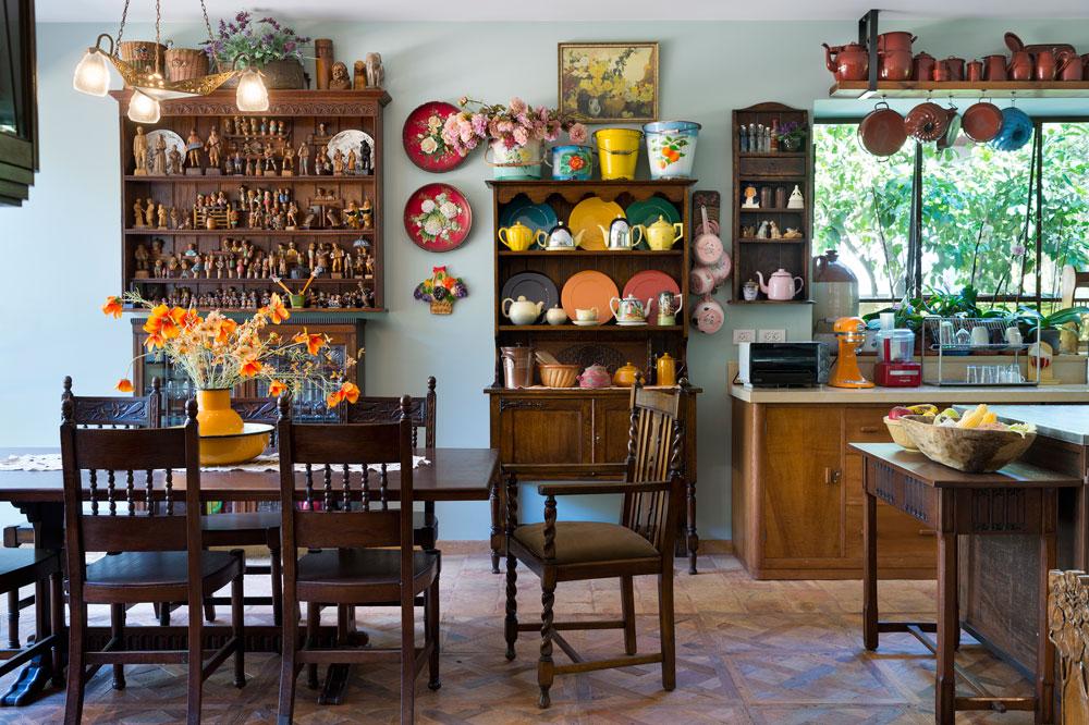 המטבח ארוך, ומשני צדיו - קרוב לחלונות גדולים שפונים החוצה - יש שתי פינות אוכל. האחת מלבנית ורשמית יותר, ולצדה אוסף מרשים של דמויות עץ שגולפו ביד אמן בבית היוצר האיטלקי ''ארני''. הרצפה עשויה מאריחי טרה-קוטה שביניהם שוקעו קורות עץ - הכל מבתים ישנים שפורקו באירופה. עשרות כלים מוצגים ומקשטים את החדר, וכל אחד מהם נבחר בקפידה (צילום: יונתן בלום)