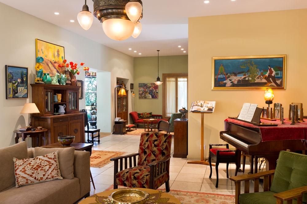 במרכז הסלון פסנתר כנף, שמעיד על מקומן המרכזי של המוזיקה והנגינה בחיי היום יום. הציורים על הקירות בסגנון נאיווי, החביב על בעלת הבית. משמאל נראית הכניסה למטבח (צילום: יונתן בלום)