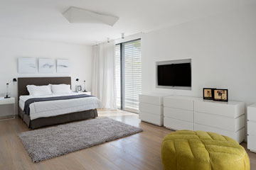 חדר השינה: פרקט עץ אלון, חלונות גדולים, נישה עם מסך טלוויזיה, שלוש שידות לבנות והדום בצבע חרדל (צילום: שי אפשטיין )