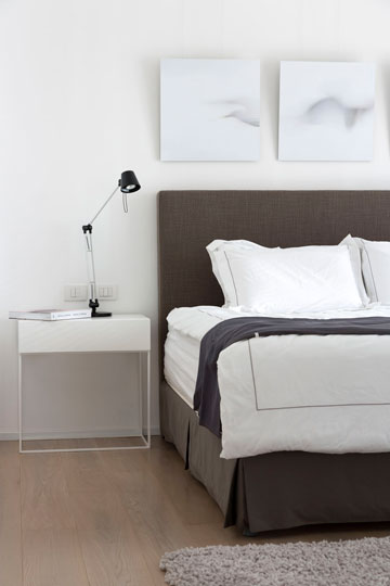 חדר שינה בצבעים רגועים: המיטה רופדה באפור, ומצידיה שתי שידות לבנות וקלילות (צילום: שי אפשטיין )