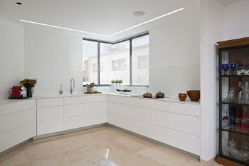 המטבח כיום. על הארונות הונח משטח קוריאן עם כיור יצוק. שני פסי תאורה בצורת האות ר' מאירים את המשטח (צילום: שי אפשטיין )