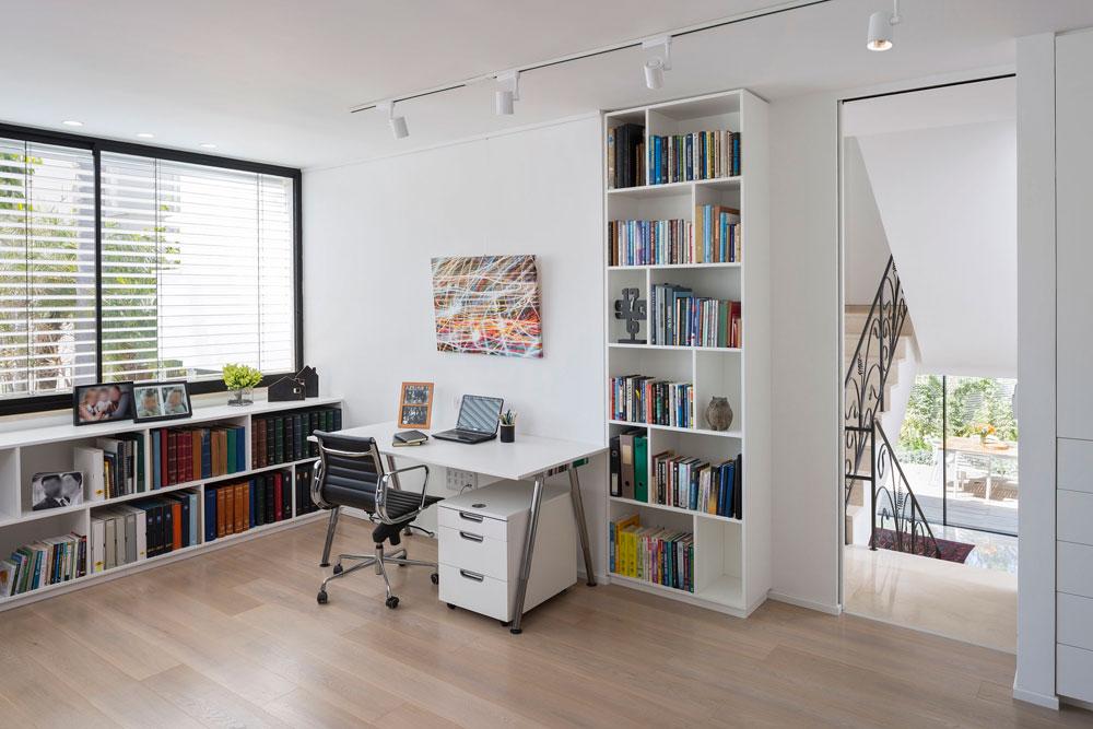 במפלס הביניים הפך חדר ההורים הישן לחדר עבודה מואר ומרווח, עם שולחן לבן, ספרייה נמוכה מתחת לחלון ושתי ספריות הניצבות משני צידיה של דלת הכניסה: האחת פתוחה והשנייה סגורה (צילום: שי אפשטיין )