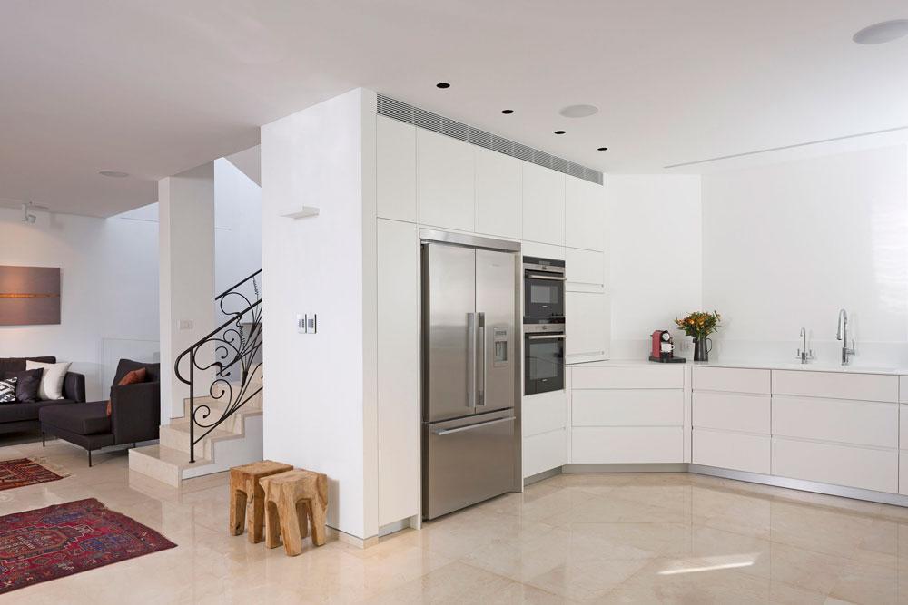 הרצפה חופתה מחדש באריחי שיש קרמה בהירים. המטבח הושאר במקומו המקורי, אך הפך לבן ומינימליסטי, וקיר אלכסוני טושטש באמצעות ארון גבוה. שמונה מדרגות עולות למפלס חדר העבודה (צילום: שי אפשטיין )
