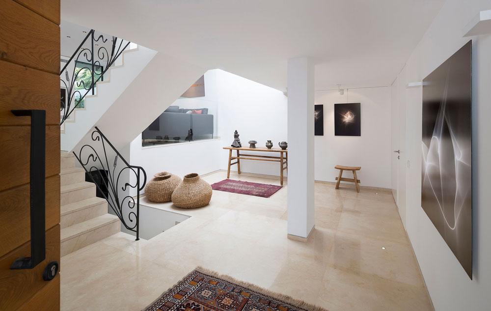 המבואה שהורחבה מוארת בעזרת חלון סקיי-לייט בתקרה. על הקירות עוד תצלומים של בעלת הבית, ומעקה זכוכית מפריד בינה לבין פינת הישיבה בסלון (צילום: שי אפשטיין )
