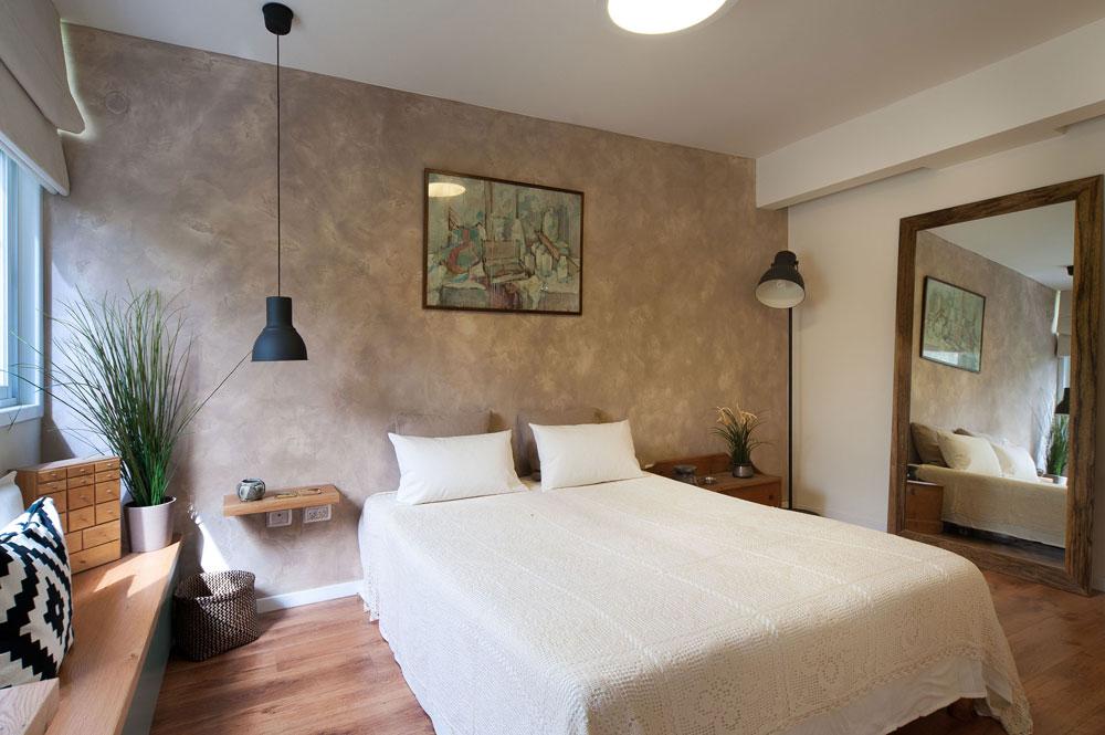 המיטה נשענת אל קיר שנצבע עם אפקט ''משופשף''. הפריטים משני צדיה אינם סימטריים, וכנגד הקיר הפנימי הושענה מראה גדולה במסגרת עץ (צילום: עמרי אמסלם)