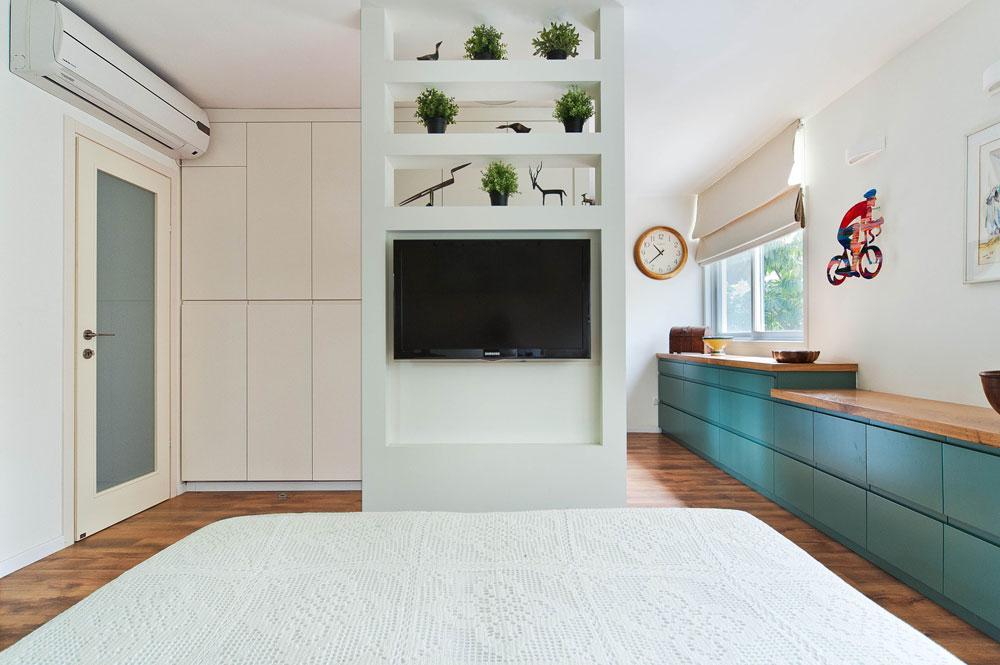 דלת הכניסה לחדר (משמאל) עשויה זכוכית. לצדה ארון לאחסון נעליים ותיקים. השידה (מימין) משתרעת לכל אורך הקיר – שבעה מטרים - ומחברת בין אזור השינה לארון של אנקורי (צילום: עמרי אמסלם)