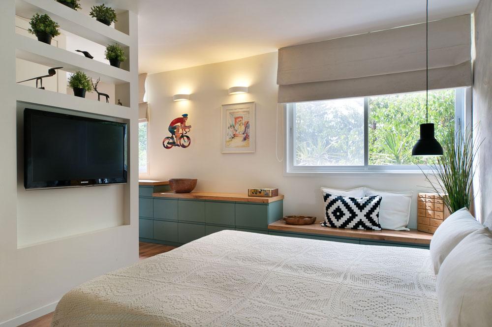 מול המיטה נבנה קטע קיר שעליו נתלה מסך טלוויזיה. בחלקו העליון תוכננו מדפים פתוחים, שעליהם הונחו חפצי נוי (צילום: עמרי אמסלם)