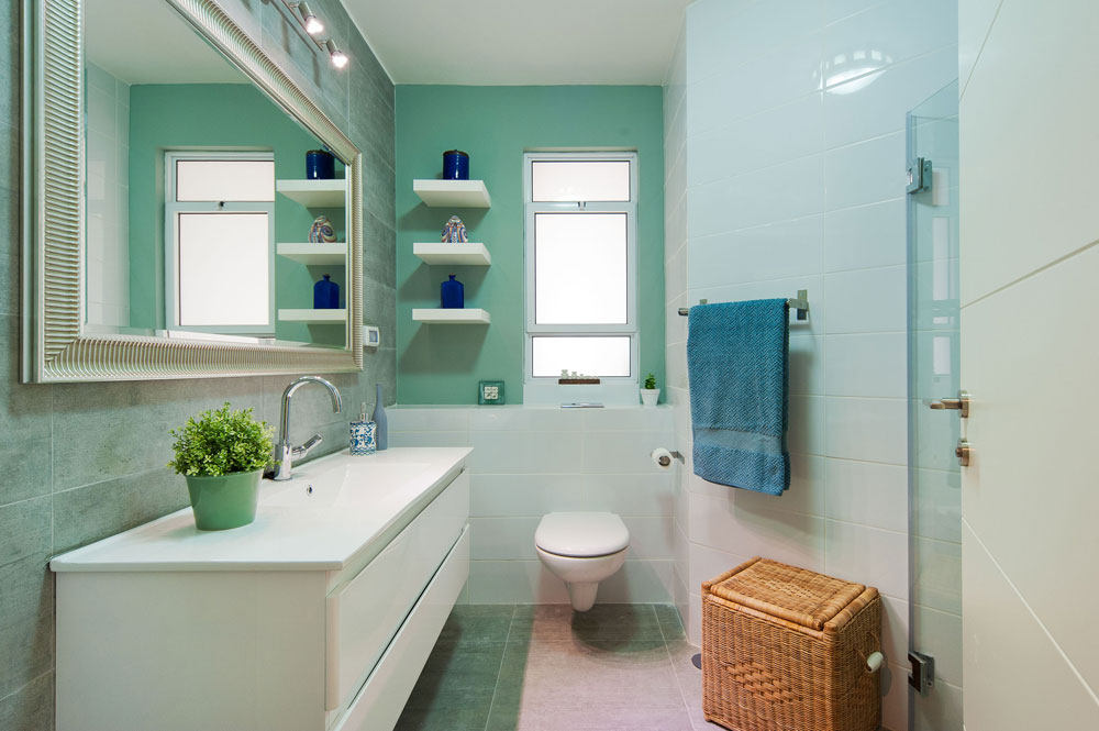 חדר הרחצה הצמוד לחדר העבודה. האמבטיה בוטלה ובמקומה נבנה מקלחון רחב. הרצפה והקיר שמאחורי הכיור חופו באריחי גרניט-פורצלן דמויי בטון, והקיר שמול הדלת נצבע בגוון ירקרק (צילום: עמרי אמסלם)