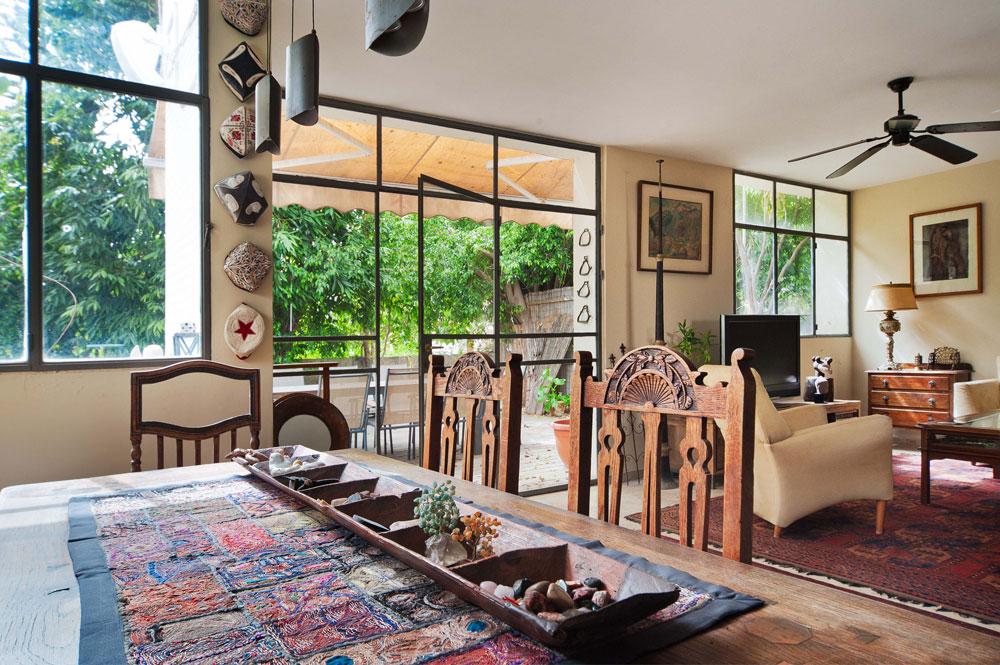 גם בסלון אוספים שונים, ופריטים מיוחדים כמו מנורה מהמאה ה-19 על שידה לצד החלון ושופר טיבטי גבוה, מימין לוויטרינה הגדולה שמובילה לגינה (צילום: עמרי אמסלם)
