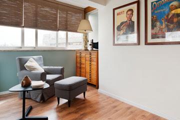 המרפסת הסגורה הוסבה לפינת קריאה בחדר העבודה, והוצבו בה כורסה והדום ישנים ושולחן צד חדש (צילום: עמרי אמסלם)
