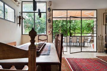 הסלון ופינת האוכל פתוחים לחצר האחורית. מימין לוויטרינה עומד שופר טיבטי גבוה שנקנה בתאילנד (צילום: עמרי אמסלם)