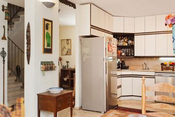 המטבח לא שופץ שנים. משמאל: גרם המדרגות המוביל לקומת חדרי השינה (צילום: עמרי אמסלם)