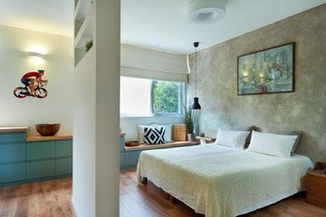 השידה בחדר השינה נצבעה בכחול-ירקרק ומעליה הונח משטח עץ. מתחת לחלון היא מונמכת והופכת לספסל (צילום: עמרי אמסלם)