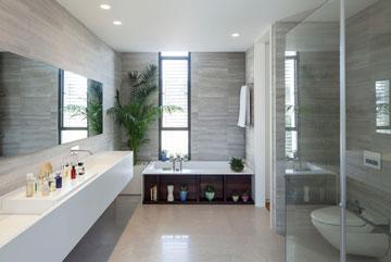 בחדר הרחצה קירות אבן ואמבטיה עם חזית עץ (צילום: עמית גרון)