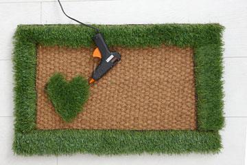 מדביקים את רצועות הדשא סביב היקף השטיח (צילום: עדי גלעד)