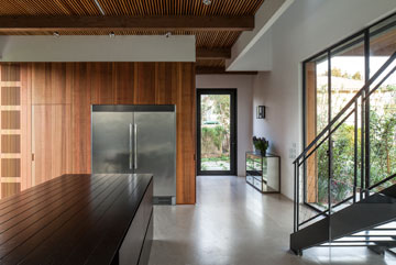 מבט מהמטבח לכיוון דלת הכניסה וקוביית המערכות, המחופה עץ ארז (צילום: עמית גרון)