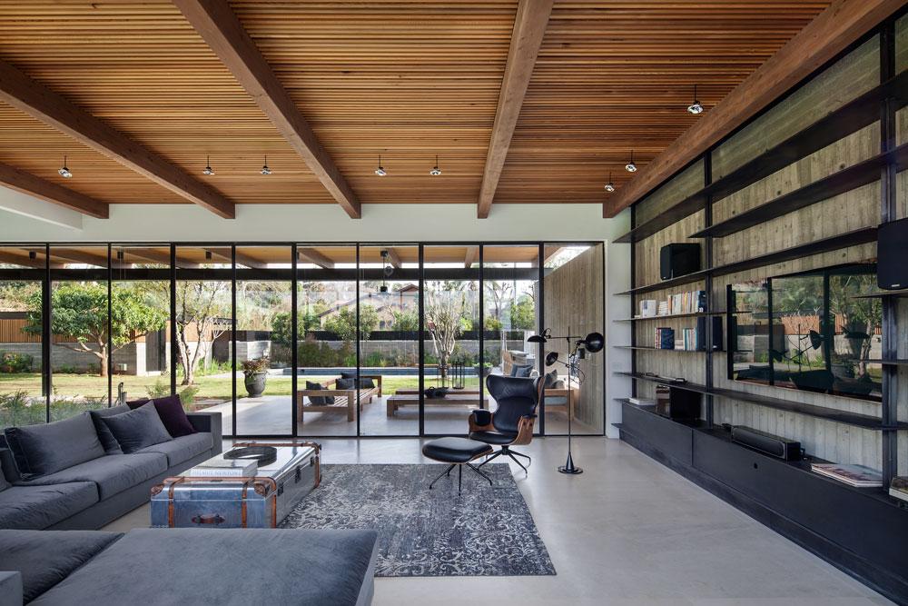גם קיר הבטון החשוף כמו חודר את ויטרינת הזכוכית, מגדיר את אזור האירוח בחוץ, ותומך בפרגולה מצדה האחד (צילום: עמית גרון)