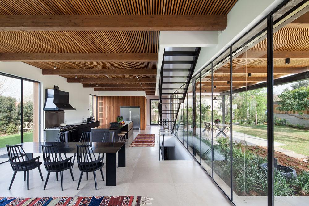 קומת הכניסה, מבט מכיוון הסלון לדלת. הקומה תחומה בקירות שקופים, שמשחררים את החלל מהמראה הכבד שיוצרת הקופסה האפורה. הרצפה מאבן והתקרה מחופה עץ (צילום: עמית גרון)