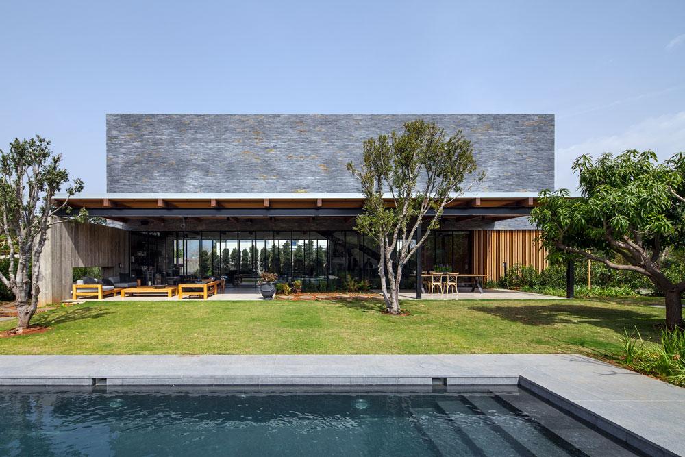 """שטח הבית 450 מ""""ר. הקומה העליונה מחופה אבנים קטנות ומאורכות של צפחה שחורה; הן מסודרות בצפיפות ומשוות לה מראה של קופסה בעלת עוצמה, המרחפת מעל קומה שקופה (צילום: עמית גרון)"""