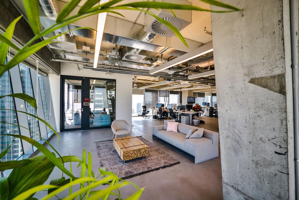בהשוואה למשרדי גוגל הססגוניים, כאן הטונים נמוכים יותר. את החללים מעטרים רהיטים מגוונים: פופים, כיסאות בר, כורסאות וכדומה. משמאל נראה מגדל דיסקונט הסמוך (צילום: איתי סיקולסקי)