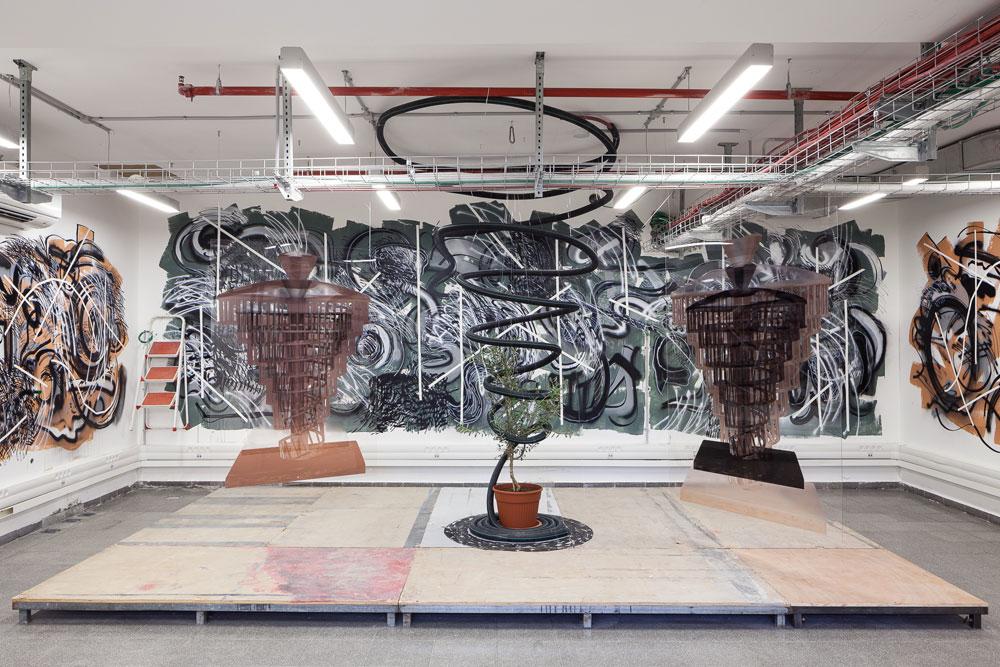 """במרתף מוצגת העבודה """"שכבות זיכרון"""" של דורון בר-אדון בשיתוף עם שחר בר-אדון - מחווה ל""""אינפרנו"""" של דנטה - העשויה עץ, פרספקס, צינור גומי, צמח, צבעי שמן, פחם וגרפיט (צילום: טל ניסים)"""