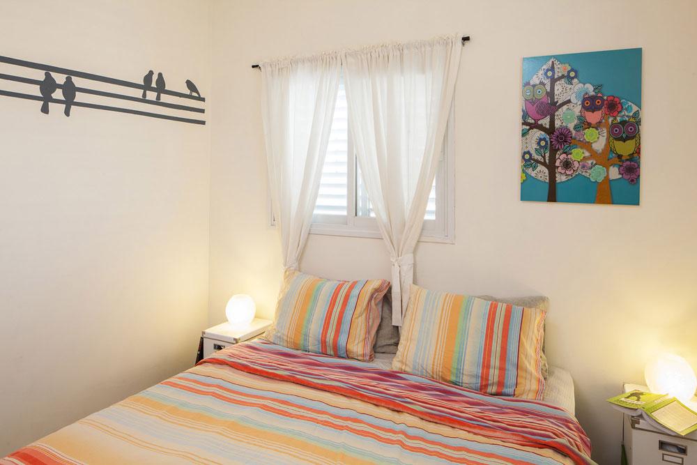 חדר השינה: השידות לצדי המיטה הורכבו מקופסאות אחסון פשוטות, והצבע שנשאר מקיר הלוח שימש לציור הציפורים (צילום: טל ניסים)