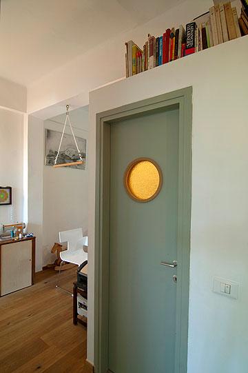 דלת חדר השירותים ב''אי''. מעבר לפינה: שולחן העבודה שבין המטבח לחדר הילדה (צילום: שי בן אפריים)
