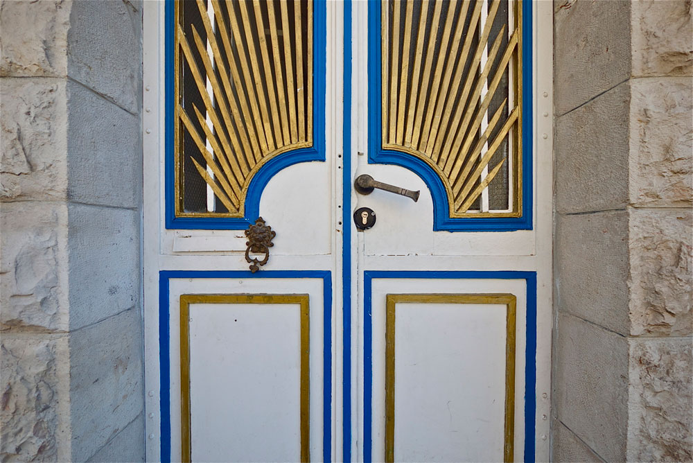 המקום: בניין לשימור בירושלים. מטראז': 180 מ''ר. תכנון ועיצוב פנים:  טלי רצהבי וגליה גלעדי מ''סטודיו taga''. דלת הכניסה המקורית שומרה, ופיתוחי הברזל שלה נצבעו כחול, לבן וזהב (צילום: איתי סיקולסקי)