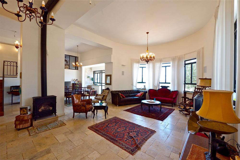 סלון מעוגל. המעצבות חשבו שנכון יותר להציב בו ספה מודרנית ועגולת קווים, אך בעלי הבית העדיפו ספה עתיקה שרופדה בבד קטיפה אדום (צילום: איתי סיקולסקי)