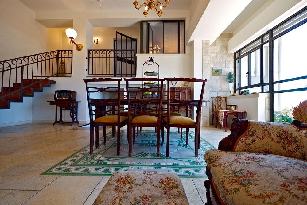 פינת האוכל הוצבה על ''שטיח'' האריחים המצוירים שנמצא בדירה. מעליו אפשר לראות את קומת הגלריה שבה חדר השינה של בעלי הבית (צילום: איתי סיקולסקי)