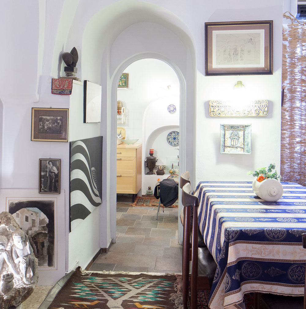 האווירה האוריינטלית והביתית ששורה על החלל הקטן והשקט, שקירותיו עבים מאוד, נובעת גם מאוסף הרהיטים והשטיחים של בני הזוג שממלא את החדר (צילום: טל נסים)