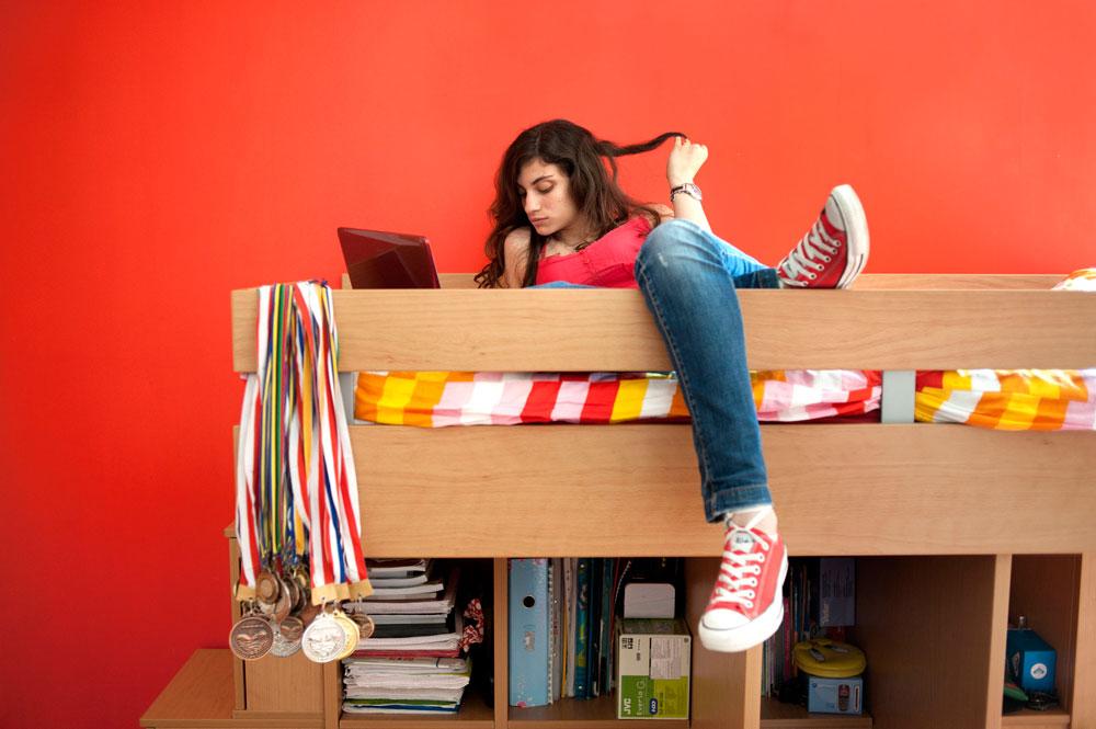 אנדראה, 2010. מתוך הפרויקט ''נערה וחדרה'' של ראניה מטר. הספורטאית הזו, ששרועה על מיטתה המקושטת במדליות שבהן זכתה, היא מביירות - אבל דבר בצילום לא מסגיר זאת (צילום: Rania Matar)