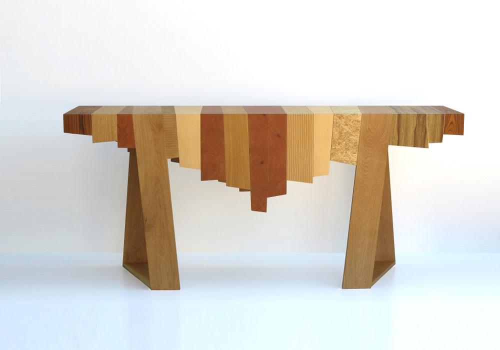 שולחן של אלי צ'יזיק, מתוך התערוכה ''זהמהיש'' בגלריה פריסקופ. צ'יזיק הופך השאריות שהושלכו מנגריות (חלקי פלטות MDF, פורמייקות צבעוניות, סנדוויץ גלוי, עץ מלא) לפלטות עתירות גרפיקה וטקסטורות, שמהן הוא מעצב רהיטים חדשים ומוקפדים (צילום: אפרת קופר)