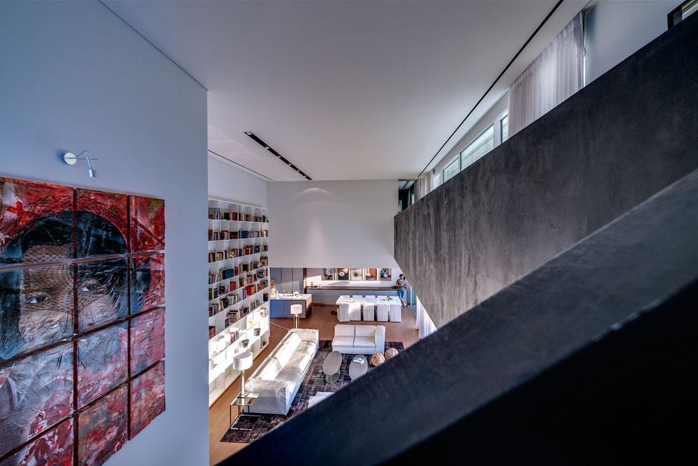 הסלון נהנה מגובה שתי הקומות. גשר פלדה עם גימור בטון בצבע שחור מוביל אל סוויטת השינה שבקומה העליונה. המטבח ופינת האוכל תוכננו בשני קווים מקבילים (צילום: איתי סיקולסקי)