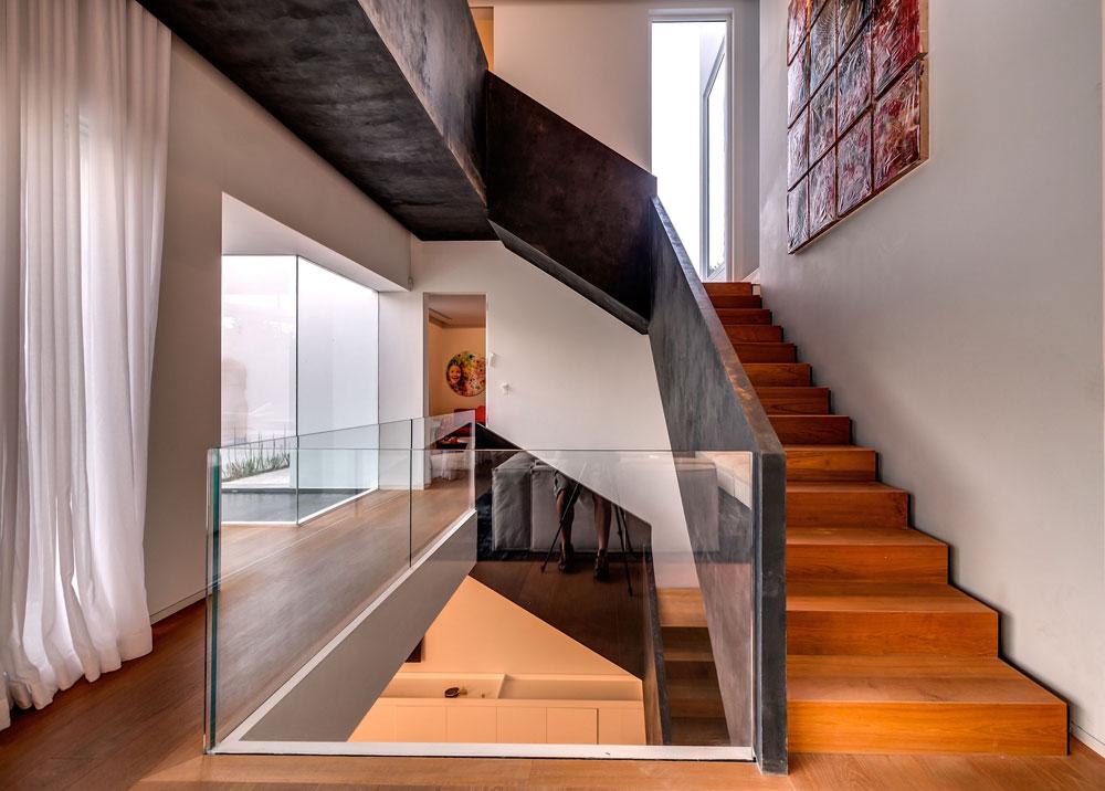 גרם המדרגות הפיסולי מוביל אל חדר השינה שלמעלה ואל מרתף גדול למטה, שנהנה מחצר אנגלית מרווחת ומוארת  (צילום: איתי סיקולסקי)