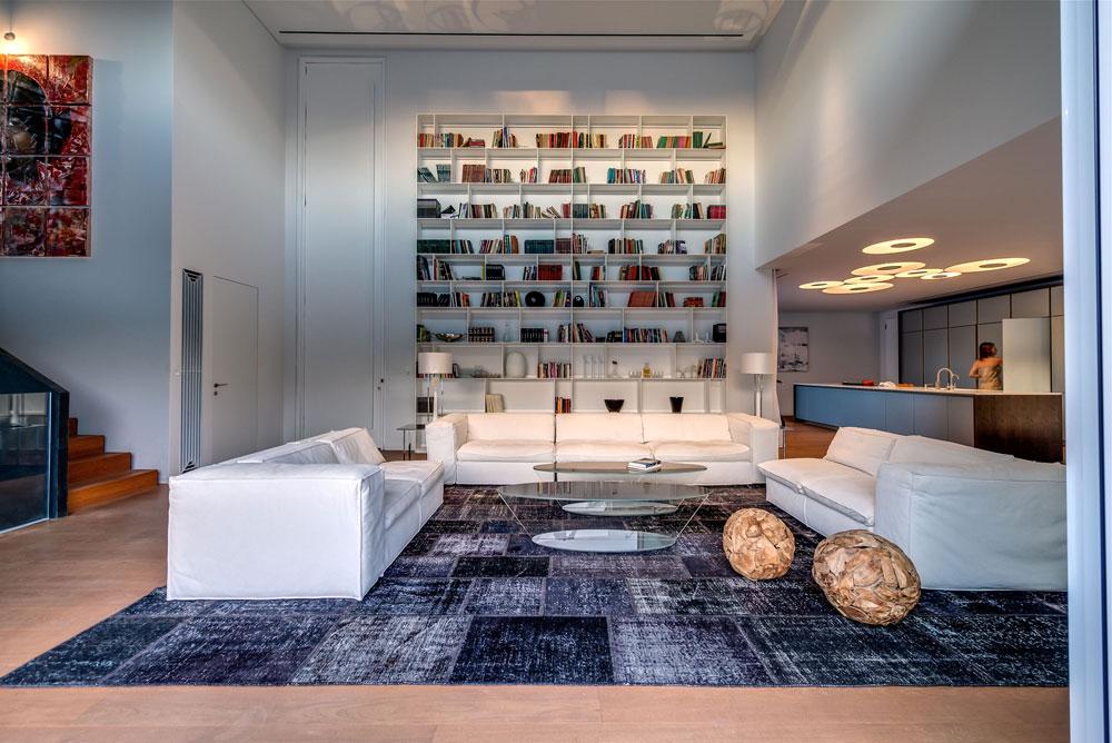 לסלון קיר זכוכית עצום שפונה לגינה ולבריכה, ועל הקיר מולו ספריית ענק, לצד דלת הכניסה שמתנשאת לגובה שישה מטרים (צילום: איתי סיקולסקי)