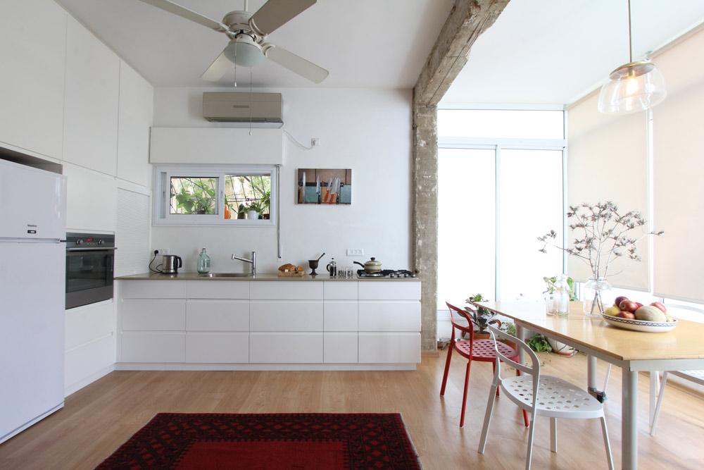 המטבח תוכנן בצורת האות ר' ונצבע לבן. פינת האוכל שובצה במה שהיתה פעם מרפסת. החלונות הגדולים הם מקור האור העיקרי של החלל הפתוח (צילום: אורי סיוון)