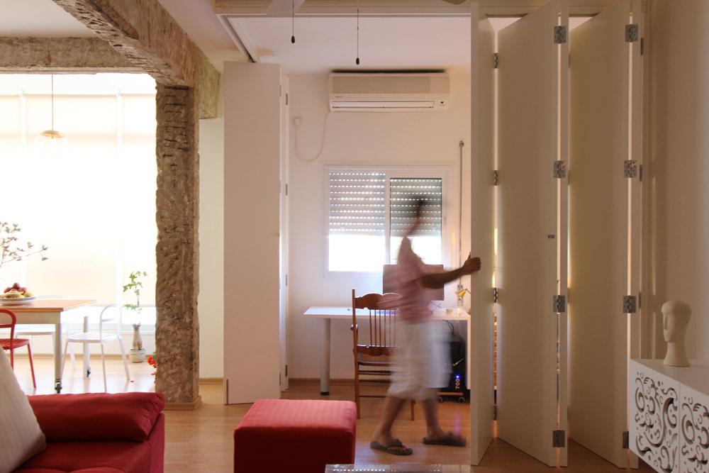 בעל הבית - מורה פרטי - יכול לסגור סביבו את חדר העבודה בשעות היום. כשהוא אינו עובד המחיצה מקופלת ונוצר מרחב פתוח, ללא הפרדות (צילום: אורי סיוון)