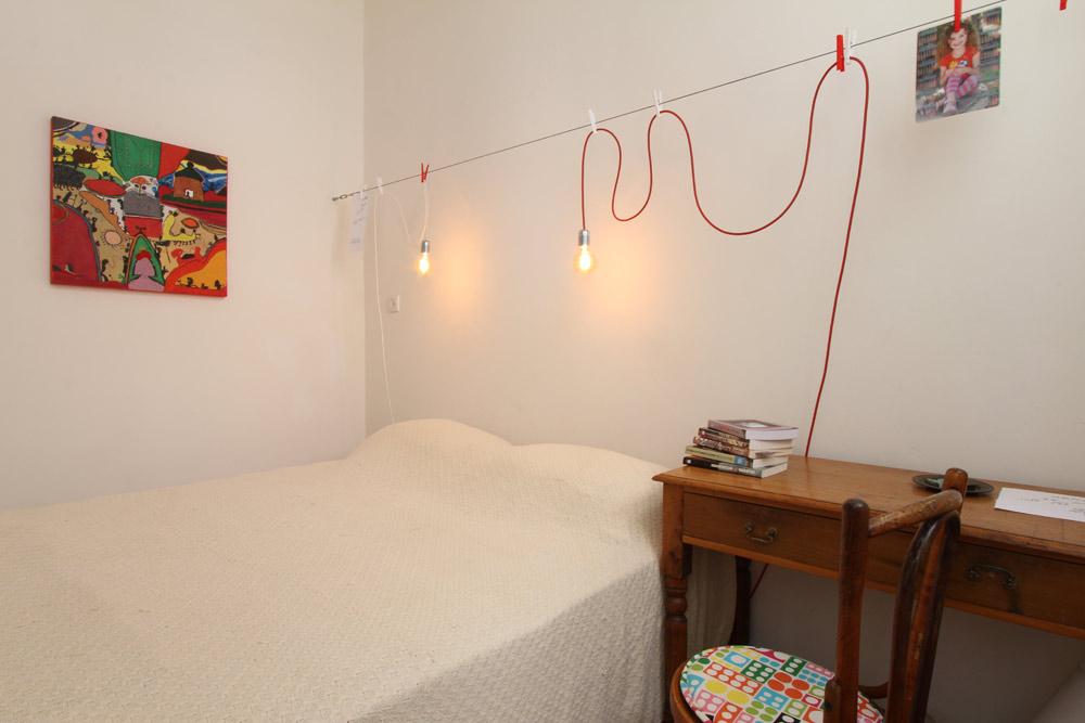 החדר משמש לשינה בלבד, ומורכב מפריטים פשוטים: מעל המיטה נמתח כבל שעליו נתלו בעזרת אטבים נורות חשופות, שאפשר להזיז לפי הצורך. על הכבל ניתן לתלות גם תזכורות ותמונות (צילום: אורי סיוון)