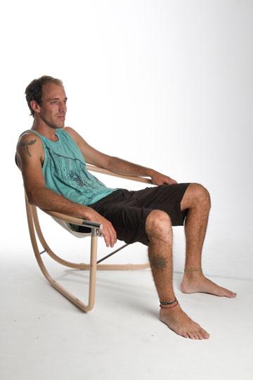 סער יושב באחד הרהיטים שעיצב ממפרשים לעבודת הגמר שלו ב-HIT, בקיץ האחרון (צילום: שלהבת אדוה)