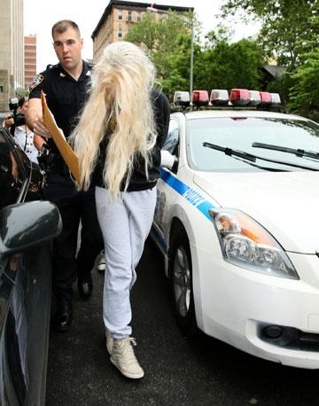 מובלת למעצר. ביינס, הפאה והשוטר המבוהל (צילום: splashnews/asap creative)