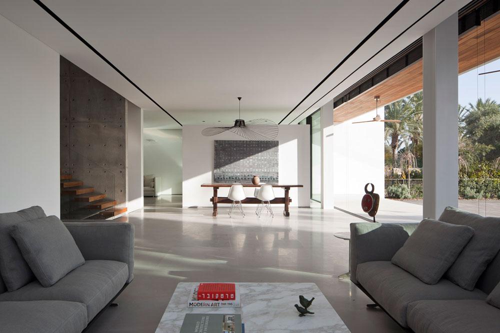 קומת הכניסה תוכננה כאילו היתה לופט גדול: מלבד קיר הבטון שנושא את גרם המדרגות יש בה רק עוד קיר אחד, שמפריד בין פינת האוכל למטבח ונבנה ''פרי סטנדינג'', מנותק מהתקרה ומהרצפה, במראה מרחף. הצבעוניות סביב מונוכרומטית והחומרים גולמיים, במטרה לאפשר לעבודות האמנות שאוספת בעלת הבית לבלוט. למשל, ציור של משה קופפרמן מעל פינת האוכל (צילום: עמית גרון)