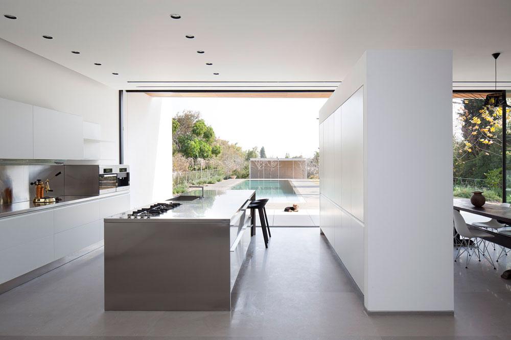 המטבח פונה אל הבריכה ונבנה כשלושה קווים מקבילים: שני קירות של ארונות ובתווך ''אי'' עבודה ואכילה (צילום: עמית גרון)