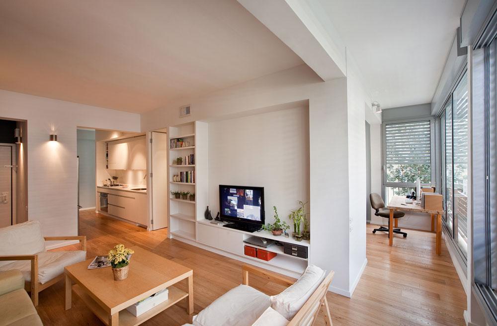 וזו דירה אחרת שתיכננו ''ספארו אדריכלים'', בשטח של 59 מ''ר. כאן חוצה את הדירה קיר עבה, שמכיל את פונקציות השירות ומערכות התשתית, ומפריד בין חדרי השינה לחלל המשותף. הקיר אינו נוגע במעטפת, כך שמתאפשרת חדירה של אור טבעי לכל חלקי הדירה, זרימת אוויר ותנועה (צילום: בועז לביא)
