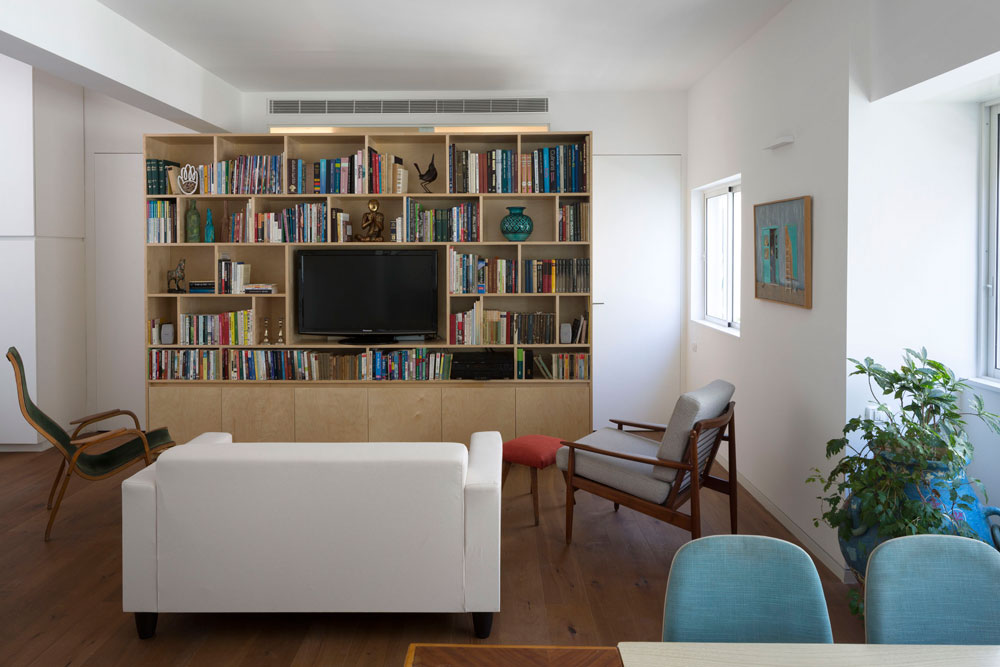 משני צדי הספרייה, שעשויה מעץ לבנה, דלתות הכניסה לחדרי הרחצה והשינה. הספרייה לא מגיעה עד לתקרה: מעליה מוקמה מערכת מיזוג האוויר וחלון צר, שמכניס אור לחדרי הרחצה (צילום: שי אפשטיין)