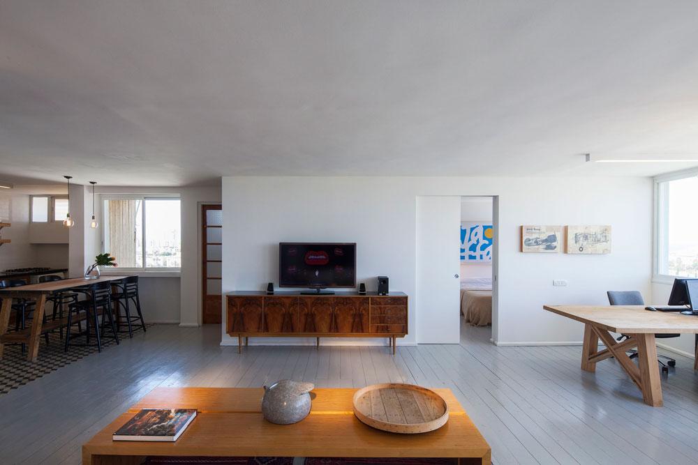דלת הזזה ברוחב 1.20 מטר מפרידה בין חדר השינה לאזור העבודה. הקיר שאליו נשענת שידת הטלוויזיה מסתיר את חדרי הרחצה והשירותים. שולחן העבודה (מימין), שעיצב זיו דניאלי, מורכב מפלטת עץ אלון מבוקע בשילוב עם רגלי עץ קרוליינה. שולחן האוכל (משמאל) הוא שולחן צלפים ישן של צה''ל, שעבר שיפוץ (צילום: אביעד בר נס)