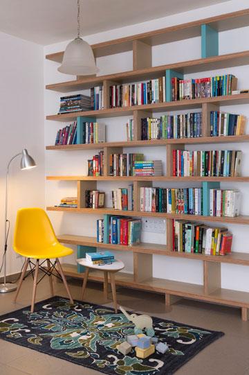 """בספרייה שולבו עץ ''סנדוויץ'"""", פורמייקה ומחיצות צבועות בטורקיז. לרגליה שטיח בגוונים משתנים של כחול (צילום: שי אפשטיין)"""